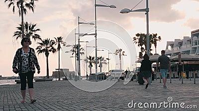 Marzo, 16, 2019/Cyprus, muelle hermoso de Paphos con los coches y trayectoria peatonal Turistas que caminan en la 'promenade' en  metrajes