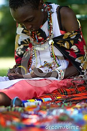 Masai woman selecting beads Editorial Stock Image