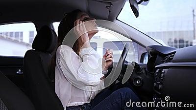 Mascara im Auto, ein hübsches Mädchen schminkt sich Gefahr hinter dem Rad Geschlagene, verspätete Geschäftsfrau zu Beginn des stock footage