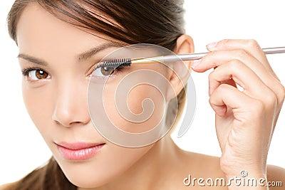 Mascara woman putting makeup on eye closeup