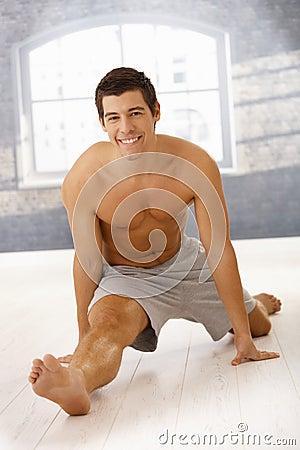 Masculine guy doing forward split in gym