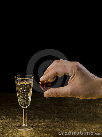 A masculine hand holds a heart and glass