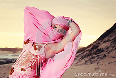 Masked Belly dancer performing on the beach