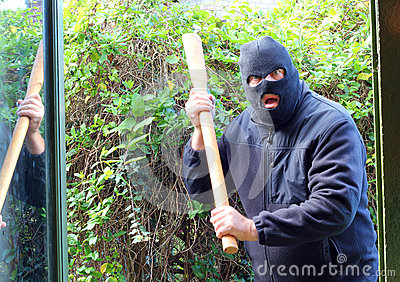 Masked burglar or robber attacking home.