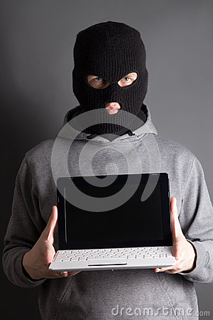 Masked man with computer over grey
