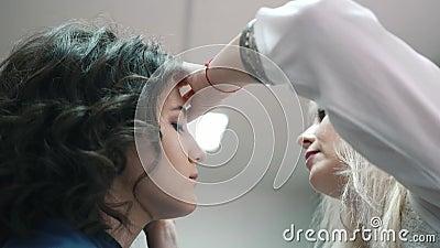 Maskenbildner Paints The Eyelashes für den Mädchen-Kunden stock video footage