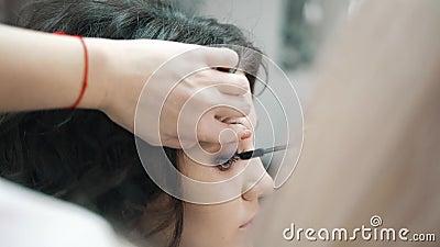 Maskenbildner Paints The Eyelashes f?r den M?dchen-Kunden stock footage