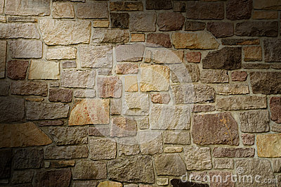 Masonry Wall of Multicolored Stone Lit Diagonally