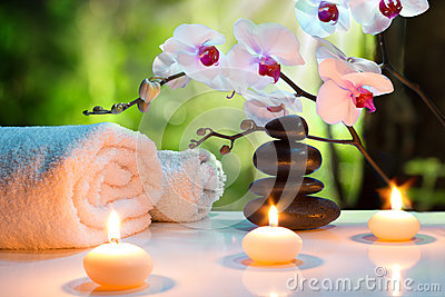 Massage composition spa with candles, orchids and black stones in garden Stock Photo