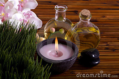 Massage oils, orchid flower, pebbles on bamboo