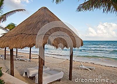 Massage Tables Under Thatched Hut on Beach