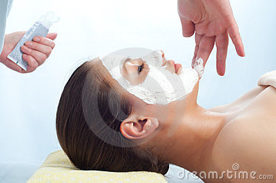 Massage therapist applying anti-aging cream