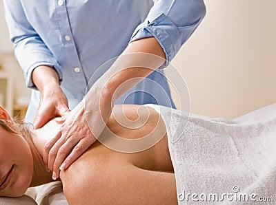 Massage therapist giving woman massage
