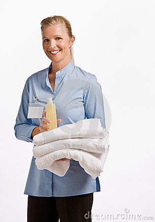 Massage therapist holding oil and towels