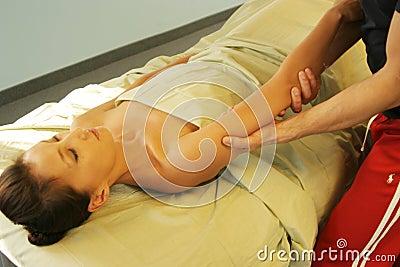 Massage therapist massaging arm