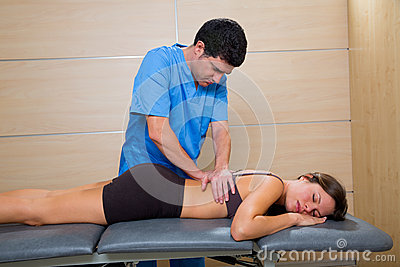 Massage therapy by physiotherapist on woman back