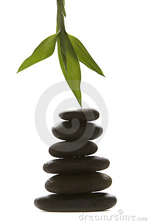 Massage therapy stones and green bamboo leaf