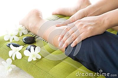 Masseur giving lady patient a leg massage
