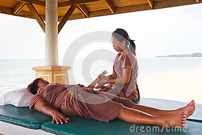 Masseuse at work on the beach in Thailand Editorial Image