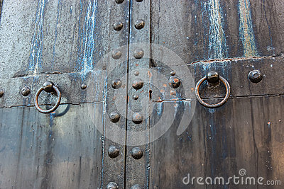 Massive old black weathered steel door with skeleton key lock