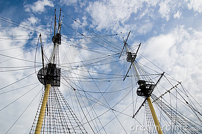 Mast of age-old ship. White cloud.