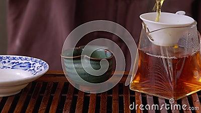 Master gießt heißes Wasser zu Gaiwan, um grünen Tee auf Holzschale zu brauen Heißes Tee schließen, durch Sieb gießen bis stock video footage