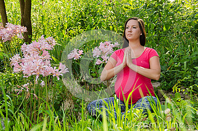 Maternity yoga peaceful meditation in field of flowers for Gardening while pregnant