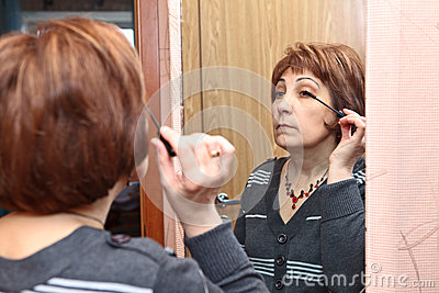 Mature adult doing make-up