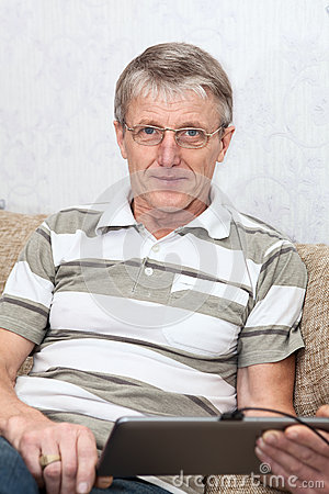 Mature adult working with tablet computer at domestic sofa