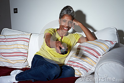 Mature African American Woman On Sofa Watching TV