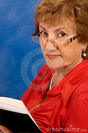 Mature attractive woman in glasses reading book