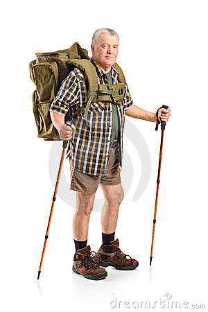 Mature with backpack holding hiking poles