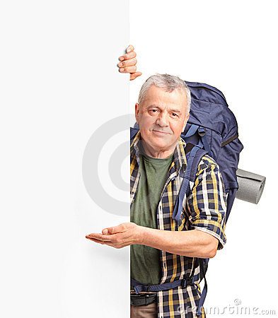 A mature backpacker gesturing on a white panel