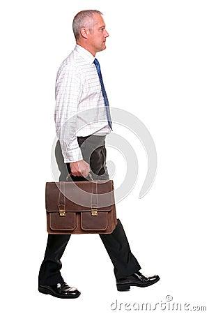 Mature businesman walking, side view.