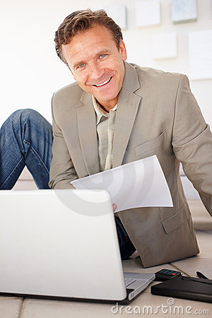 Mature business man working while on the floor