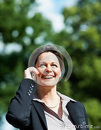 Mature business woman using a cellphone outdoors