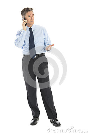 Mature Businessman Gesturing While Using Smart Phone