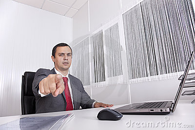 Mature businessman at the office pointing to you