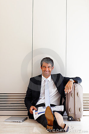 Mature businessman sitting on floor with luggage