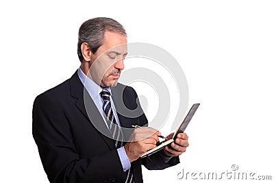 Mature businessman taking notes