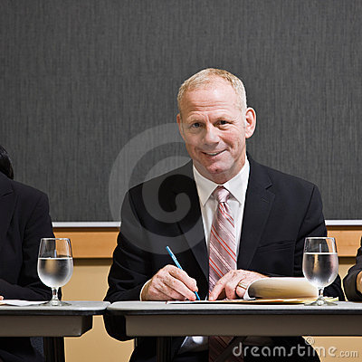 Mature businessman writing notes at table