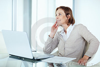 Mature businesswoman daydreaming while at work