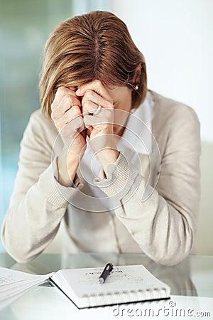 Mature businesswoman under stress sitting at desk