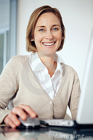 Mature businesswoman working on laptop at her desk