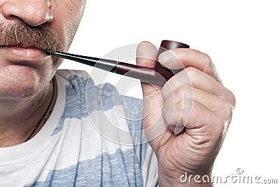 Mature caucasian man holding smoking pipe in hand