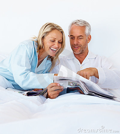 Mature couple in bed reading newspaper