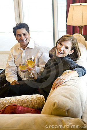 Mature couple drinking wine together on couch
