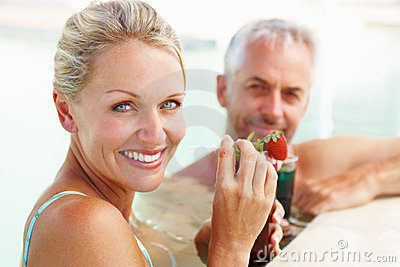 Mature couple with drinks relaxing by the pool