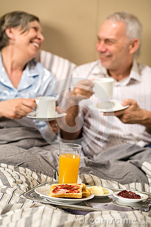 Mature couple enjoying breakfast at hotel room