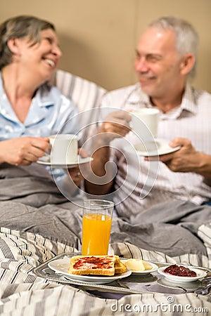 Mature couple enjoying breakfast at hotel room